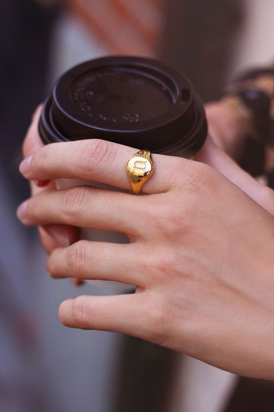 gold signet ring | woman holding coffee | Girlfriend Is Better