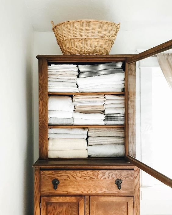 midsummer hygge | linen cabinet vintage wood rattan basket organization | Girlfriend is Better